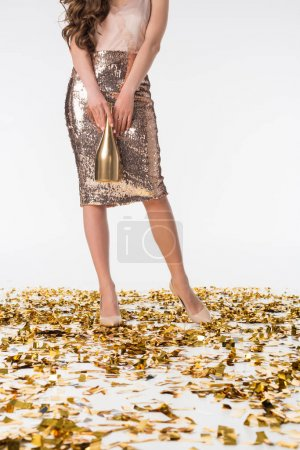 cropped image of woman standing on confetti in silver skirt and holding bottle of champagne