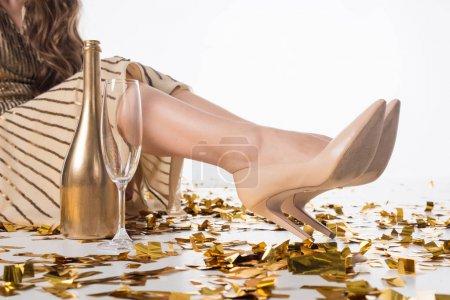 Photo pour Image recadrée de femme assise sur le sol avec bouteille de champagne et verre - image libre de droit