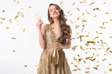 Photo pour Souriant attrayant femme debout avec champagne sous confettis tombant isolé sur blanc - image libre de droit