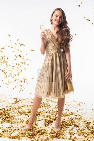 attractive woman standing with bottle and glass of champagne under falling confetti isolated on white