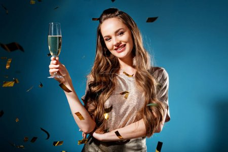smiling attractive woman standing with glass of champagne under falling confetti isolated on blue