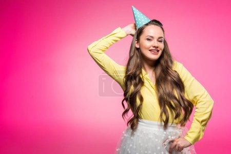 attraktive Frau posiert mit Partyhut isoliert auf rosa