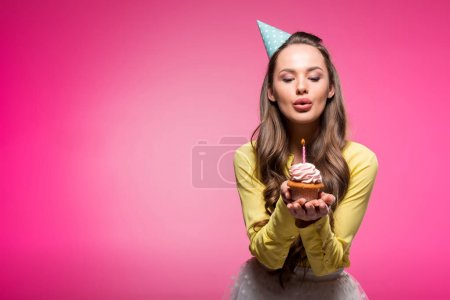 Photo for Attractive woman with party hat holding cupcake and blowing out candle isolated on pink - Royalty Free Image