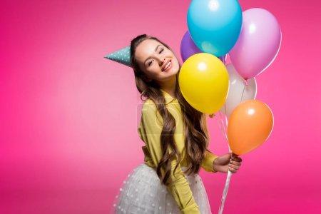 Foto de Mujer atractiva posando con sombrero de fiesta y globos aislados en rosa - Imagen libre de derechos