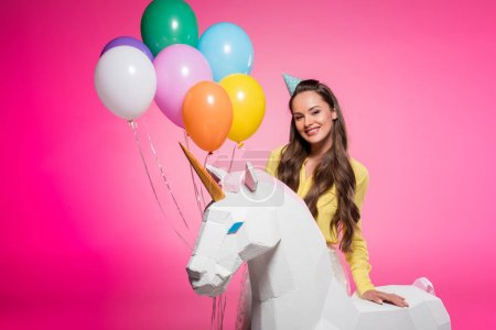 attractive woman with party hat, balloons and unicorn toy isolated on pink