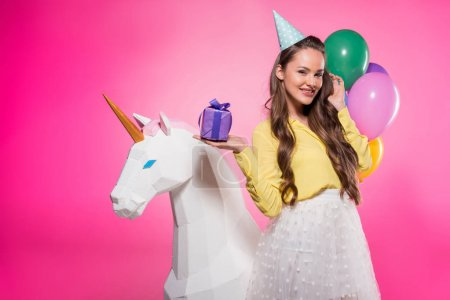 beautiful woman with party hat and present isolated on pink