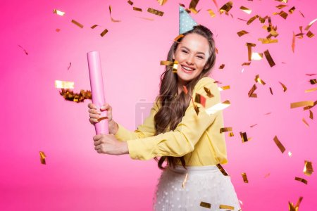 attractive woman with party hat under falling confetti isolated on pink