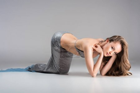 attractive woman with mermaid tail leaning on elbows and looking at camera