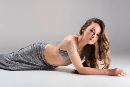 Photo for Attractive woman lying on floor in silver skirt and top and looking at camera - Royalty Free Image