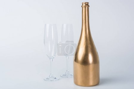 golden bottle of champagne and empty glasses on white surface