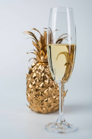 glass of champagne and golden pineapple on white