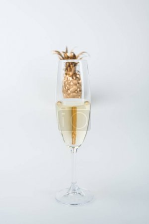transparent glass of champagne and golden pineapple isolated on white