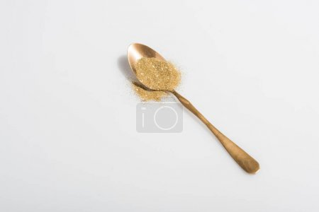 golden spoon and bright sand on white