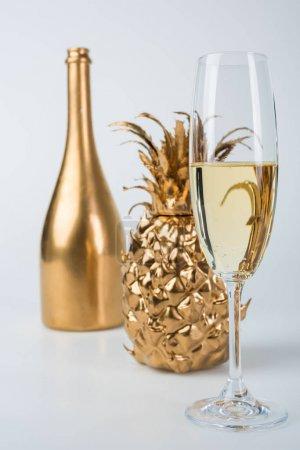 golden bottle of champagne, pineapple and glasses on white