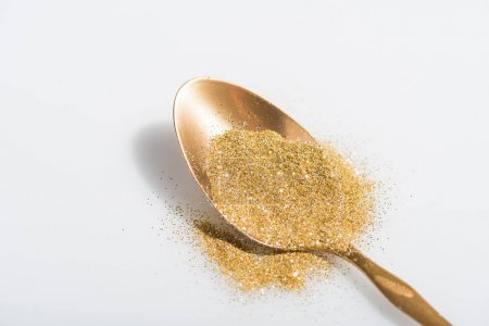 golden spoon and bright glitter on white