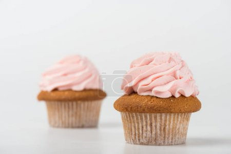 two tasty cooked pink cupcakes on white