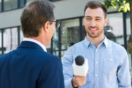 professional news reporter interviewing successful businessman with microphone