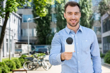 smiling male news reporter taking interview with microphone
