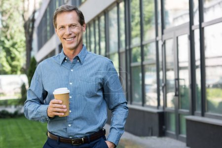 smiling businessman posing with disposable cup of coffee near office building