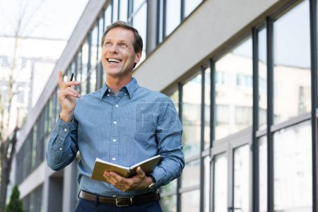 smiling businessman with diary having idea and pointing up near office building