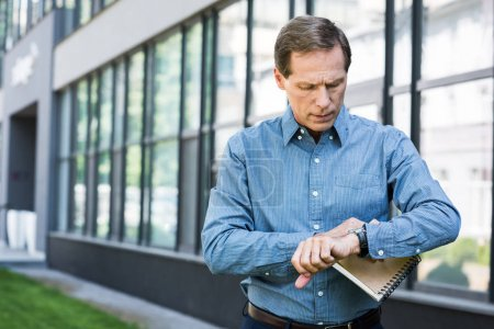 mature businessman with diary looking at wristwatch near office building