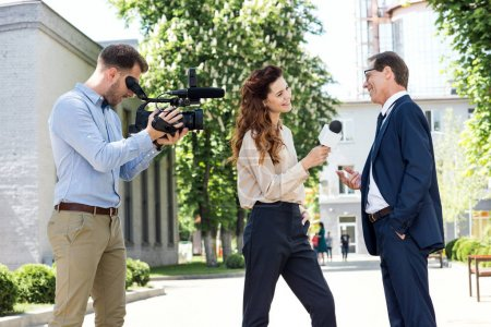 cameraman and female newscaster interviewing businessman