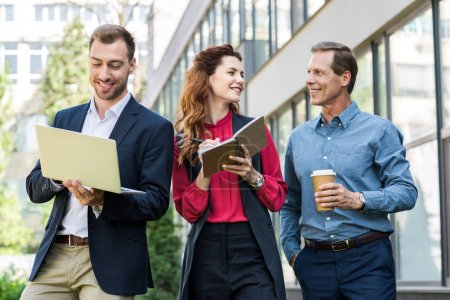 cheerful professional business team with disposable cup of coffee working together with laptop and diary