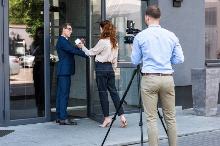 professional cameraman and journalist with businessman refusing interview