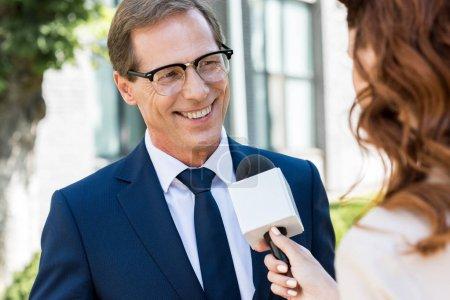 female journalist taking interview with cheerful mature businessman in formal wear