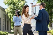 professional cameraman and news reporter interviewing businessman