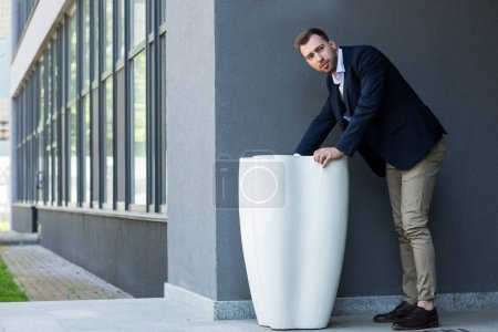 businessman in formal wear standing at garbage bin near office building