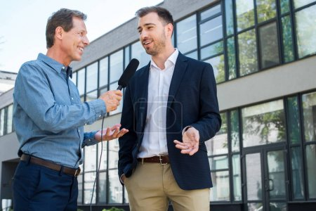 professional mature journalist interviewing successful businessman with microphone