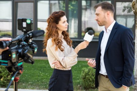beautiful serious female news reporter taking interview with businessman