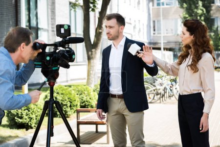 cameraman and professional news reporter with businessman refusing interview