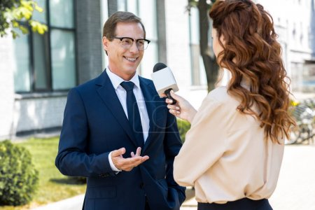 anchorwoman with microphone interviewing professional mature businessman