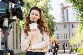 attractive serious news reporter with microphone looking at digital video camera