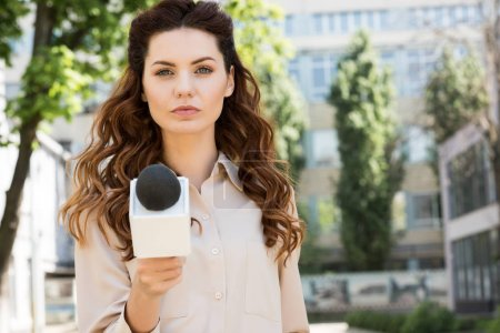 attractive serious female journalist taking interview with microphone