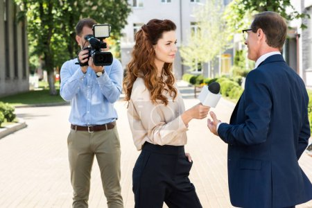 professional cameraman with digital video camera and news reporter interviewing businessman with microphone