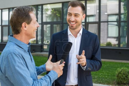 professional mature journalist interviewing public cheerful businessman
