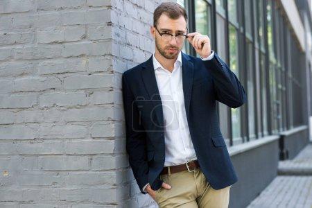 confident stylish businessman in eyeglasses posing near office building
