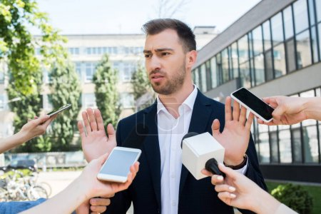 journalists interviewing serious businessman with microphones and smartphones