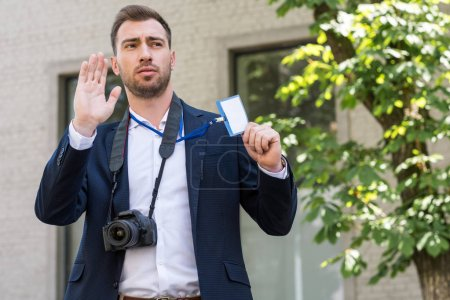 male photojournalist with digital photo camera gesturing and showing press pass