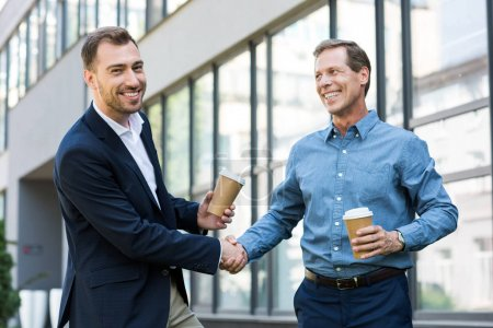 Photo for Smiling businessmen with disposable cups of coffee shaking hands near office building - Royalty Free Image