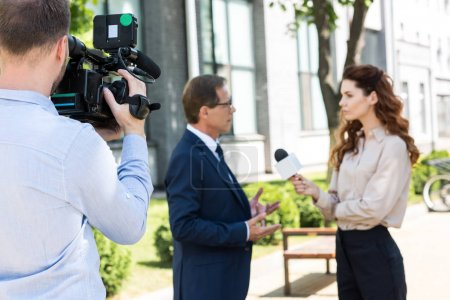 selective focus of professional cameraman with digital video camera and news reporter interviewing executive businessman