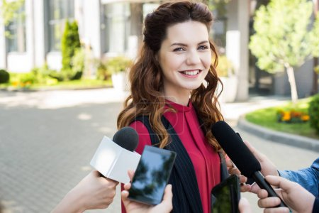 journalists interviewing public successful businesswoman with microphones and smartphones
