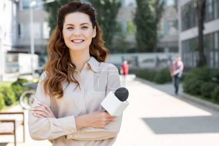 attractive cheerful female journalist holding microphone