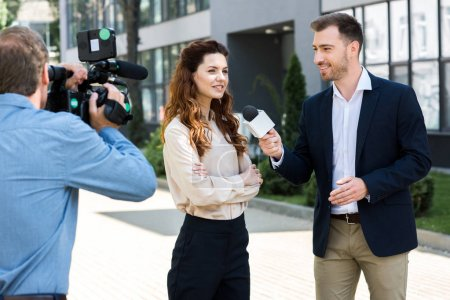 professional cameraman and male news reporter interviewing smiling businesswoman