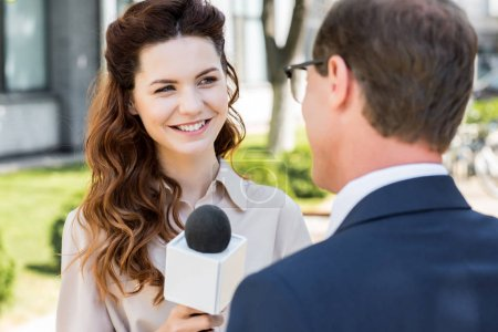 cheerful anchorwoman with microphone interviewing businessman