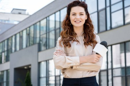 attractive smiling female journalist holding microphone and standing near office building