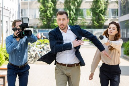 businessman running from journalists with digital video camera and microphone